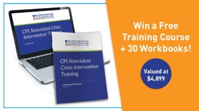 A laptop featuring an online course from Crisis Prevention Institute and a workbook.
