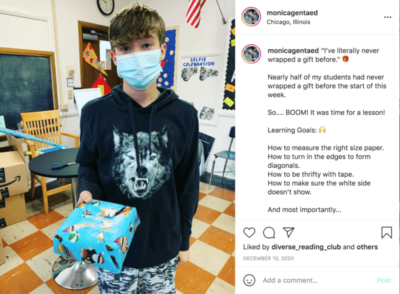 Student with mask on holds up a wrapped gift in blue patterned paper