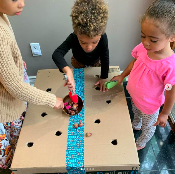 Three children using tweezers to drop acorns through a cardboard box with small holes cut in it