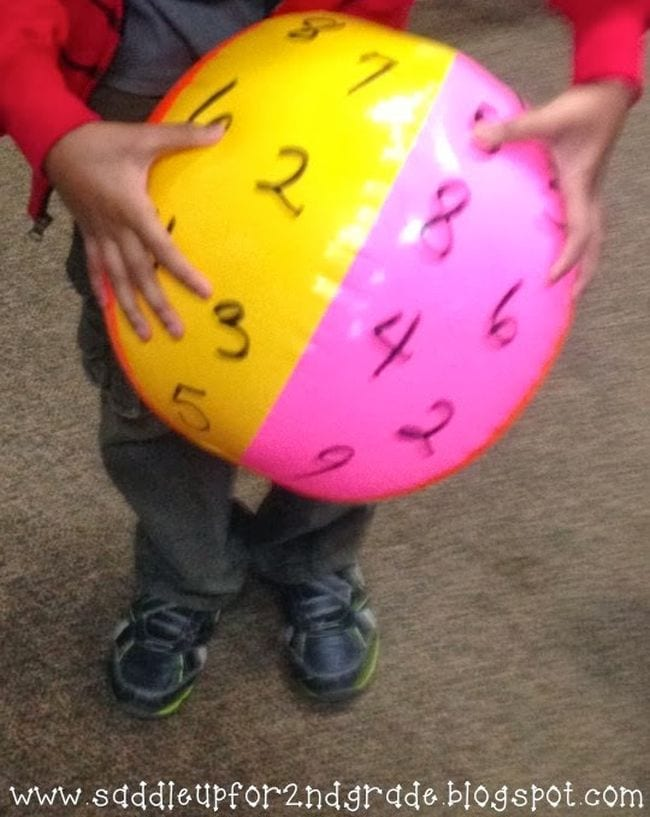 Student holding a beach ball marked with numbers (Active Math Games)