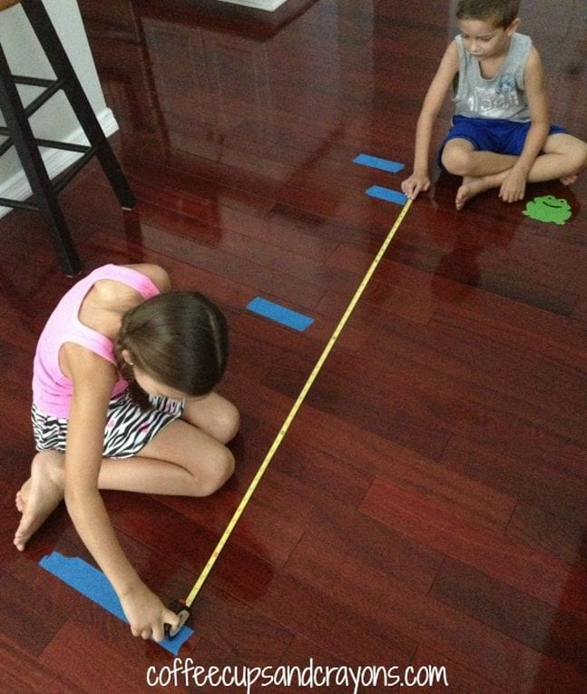 Two children measuring tape lines on the floor