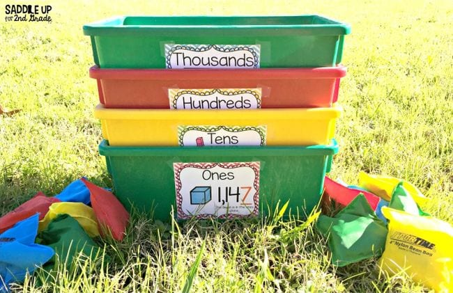 Plastic bins labeled thousands, hundreds, tens, and ones sitting on the grass with beanbags (Active Math Games)