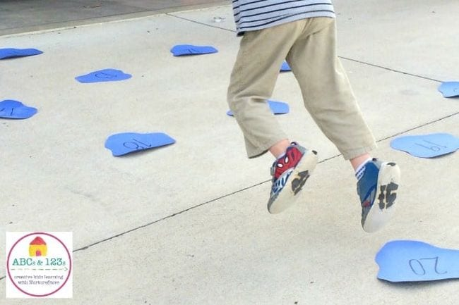 Student jumping around on construction paper puddles labeled with numbers (Active Math Games)