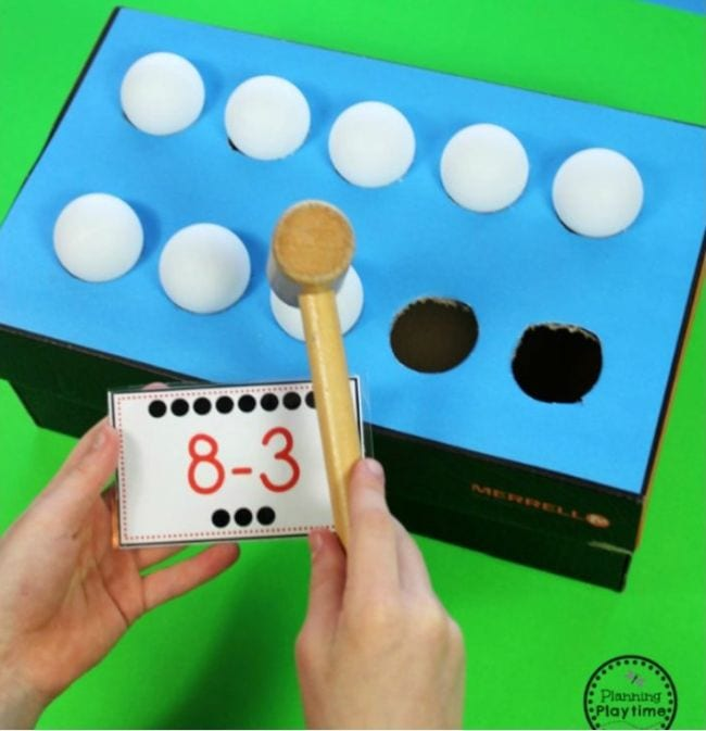 Student's hand holding a wood mallet and card saying 8 minus 3 over a box with ping pong balls resting in holes