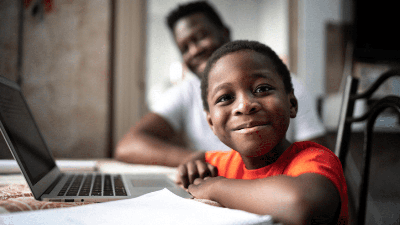 African American boy and his father studying on a laptop when instructors is teaching reading remotely