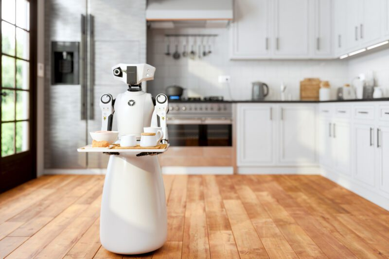 Robot Maid Holding A Tray And Serving Food And Drink In Modern Domestic Kitchen With Blurred Background. Artificial Intelligence And Smart Robotics Concept.