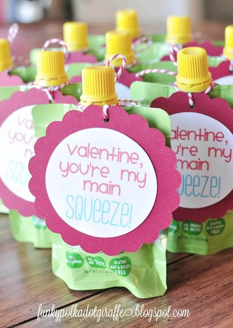"""Group of apple sauce squeeze pouches with round valentine cards that say, """"Valentine, you're my main squeeze!"""""""