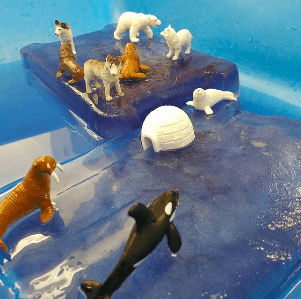 Frozen ice blocks, arctic animal figurines, and water in a sensory table for classroom sensory play