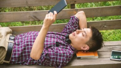 asian teen reads an ereader on a park bench teens are reading less