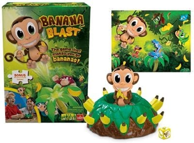 Game box, monkey puzzle and game setup with monkey sitting on a mound of bananas for the Banana Blast game