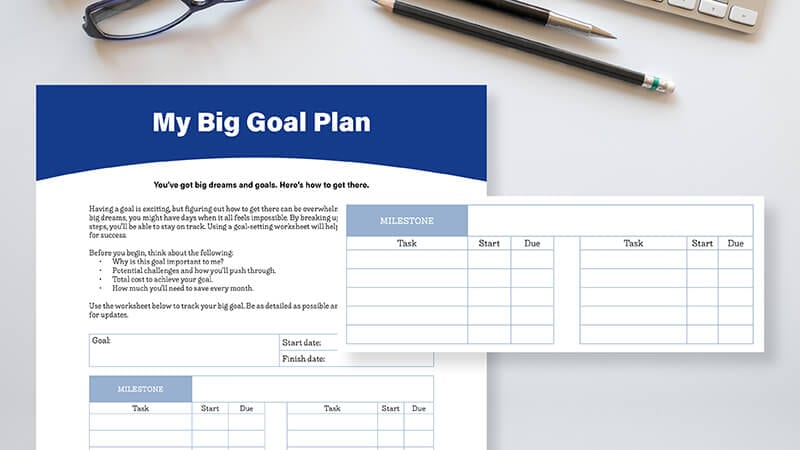 Closeup of a goal planning worksheet on a white desk with a pair of eyeglasses and two pencils