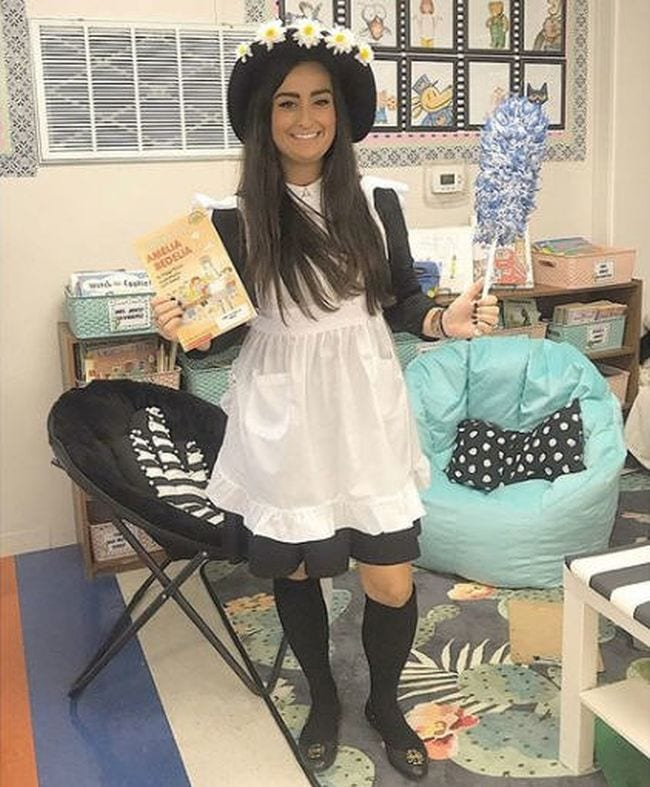 Woman wearing black dress, white apron, black hat with daisies, and carrying a feather duster (Book Character Costume Ideas)