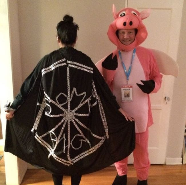 Woman wearing black cape with spiderweb that says Some Pig, with man wearing pig costume