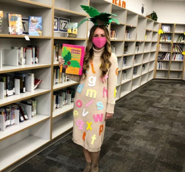 Woman wearing palm leaves on her head and covered in alphabet letters, carrying the book Chicka Chicka Boom Boom