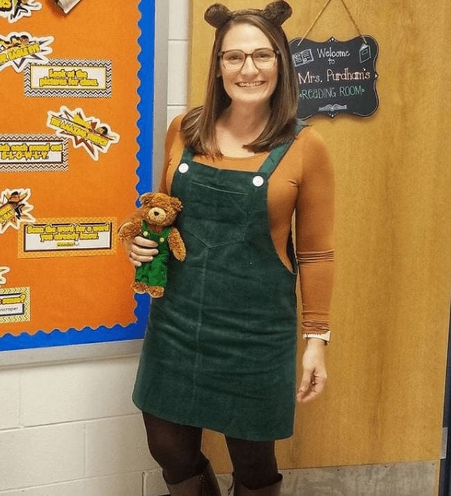 Woman wearing green corduroy jumper and teddy bear ears, carrying a matching teddy bear (Book Character Costume Ideas)