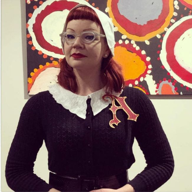Woman wearing puritan collar and bonnet with a large scarlet letter A on her sweater (Book Character Costume Ideas)