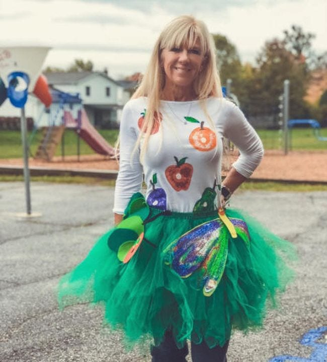 Woman wearing a green tutu and white shirt covered with pictures of food (Book Character Costume Ideas)
