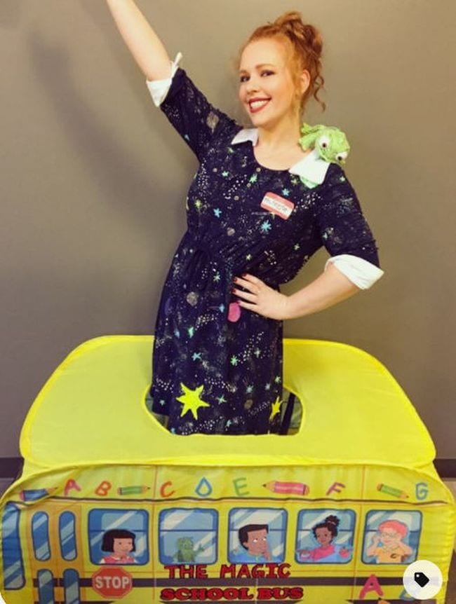 Woman wearing a space themed dress standing in a small school bus (Book Character Costume Ideas)
