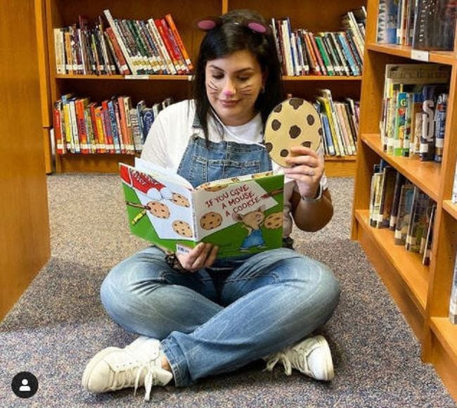 Woman in blue overalls and mouse ears holding a large paper cookie and reading a book (Book Character Costume Ideas)