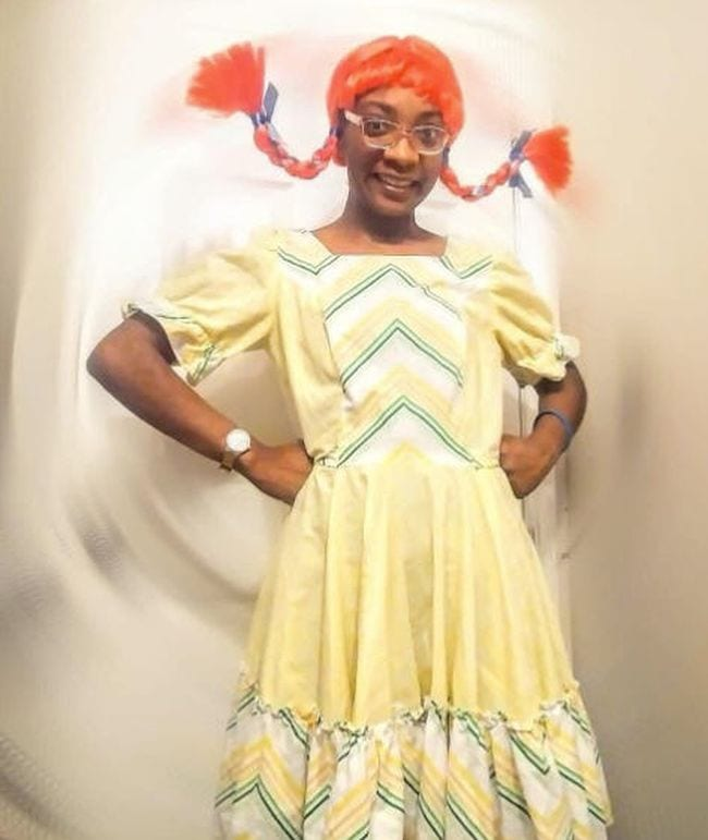 Woman wearing yellow peasant dress and red wig with horizontal braids