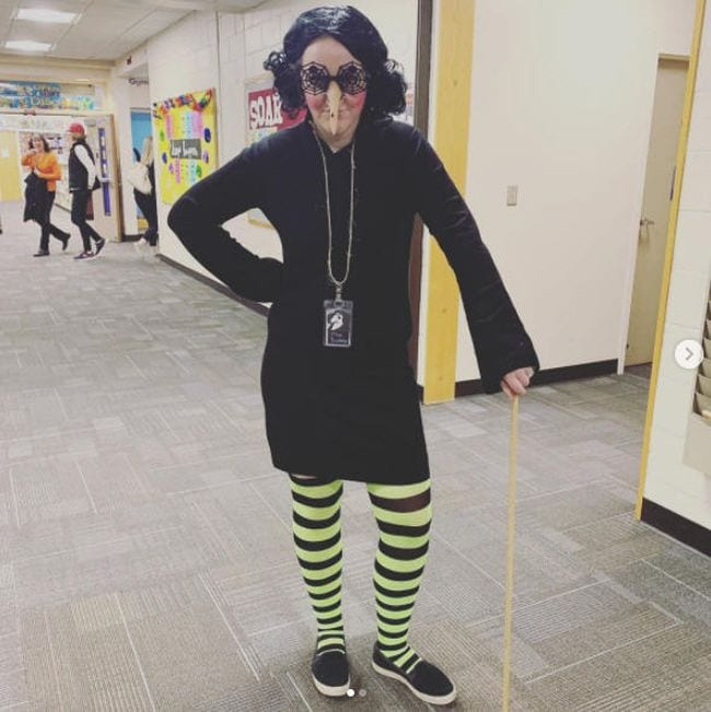 Woman wearing black dress, yellow and black striped stockings, and long fake nose (Book Character Costume Ideas)