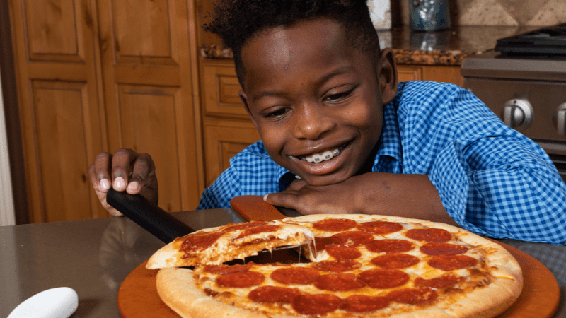 African American boy wearing braces smiling and looking at pepperoni pizza from Little Caesars Fundraising