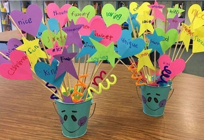 colorful buckets on a classroom desk filled with compliments made from sticks and colored paper