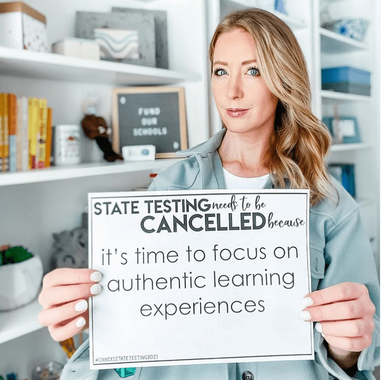 Teacher holding sign to support state testing being cancelled in 2021