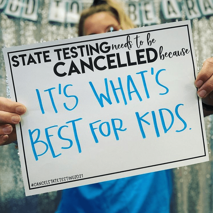 Teacher holding sign that supports canceling state tests