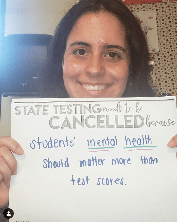 Teacher holds sign asking to cancel state testing for the mental health of kids