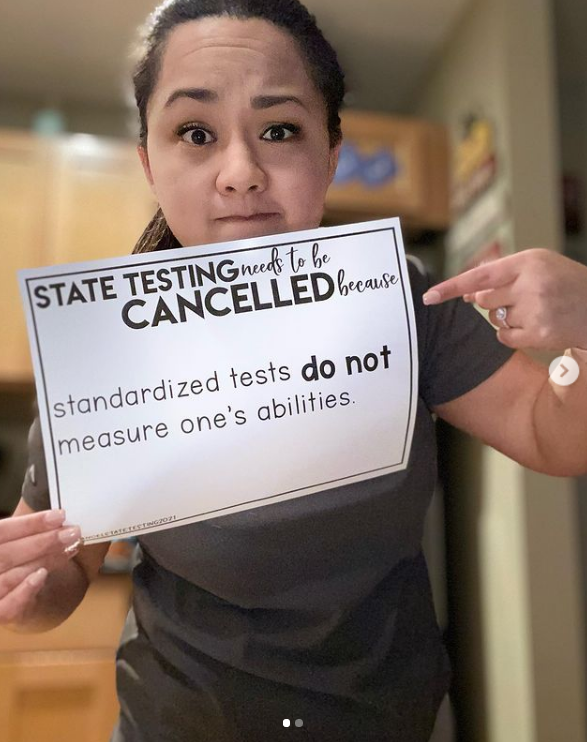 Teacher holding sign against standardized tests