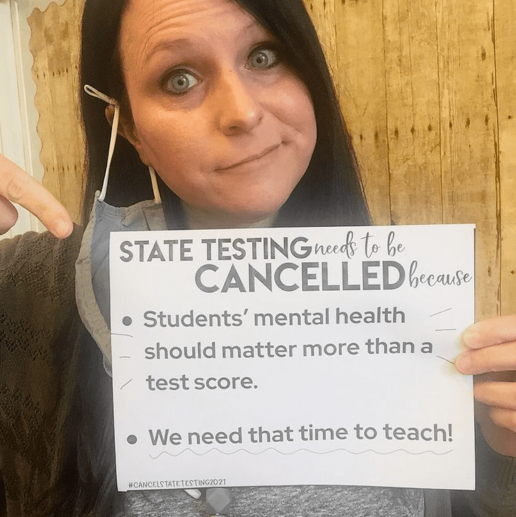 Teacher holding sign to support cancel state testing movement