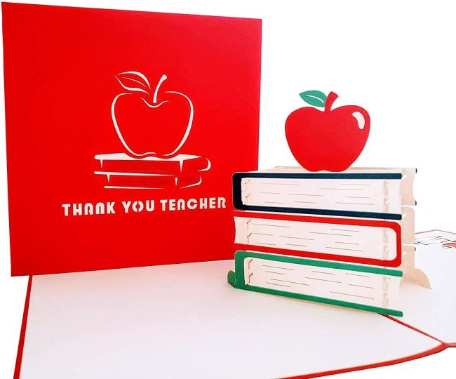 Greeting card that opens to display 3D book stack with apple on top