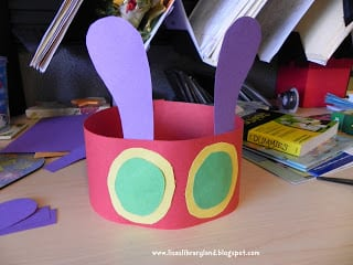 Children's headband made from construction paper- red for the band, purple for the antennae and green and yellow for the eyes