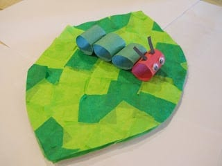A caterpillar craft made from rings of construction paper connected together sitting on top of a leaf made from green tissue paper squares