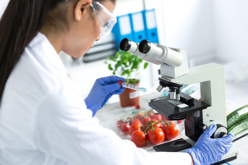 Female microbiologist using microscope in laboratoty