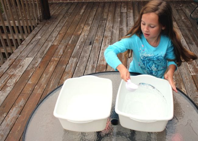 Young student scooping water from one plastic container to another (Circulatory System Activities)