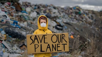 Child in raincoat in front of dump with Save Our Planet sign
