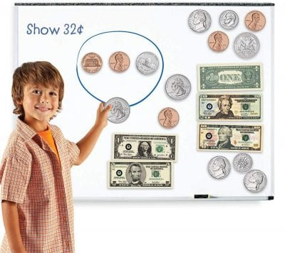 Student pointing at a board with coins and dollar bills on it -- 1st grade classroom supplies