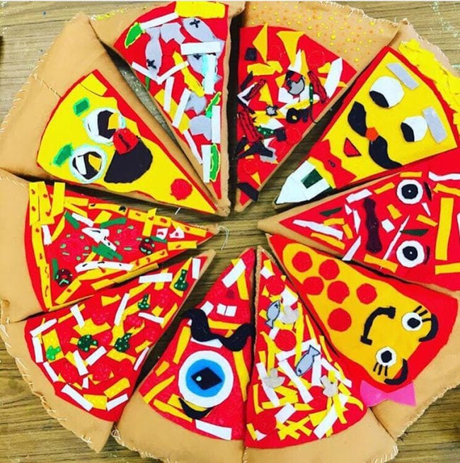 Pizza slice shaped pillows put together to form a large plush pizza