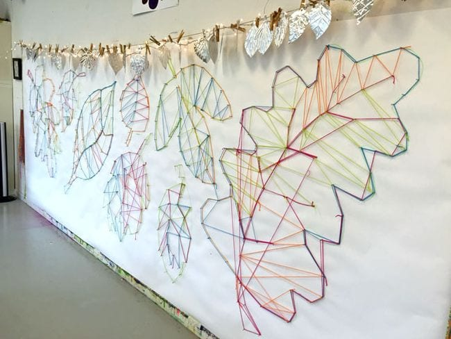 Large leaf outlines made from string hung between nails on the wall