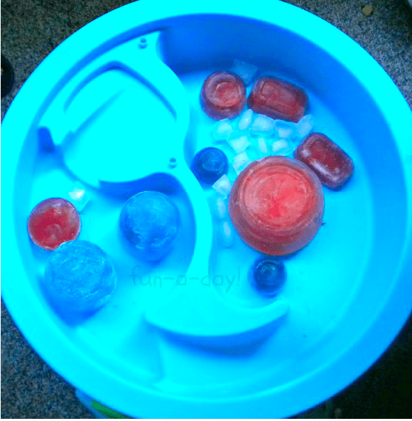 Blocks of colored ice in a water table made by freezing colored water in containers and balloons