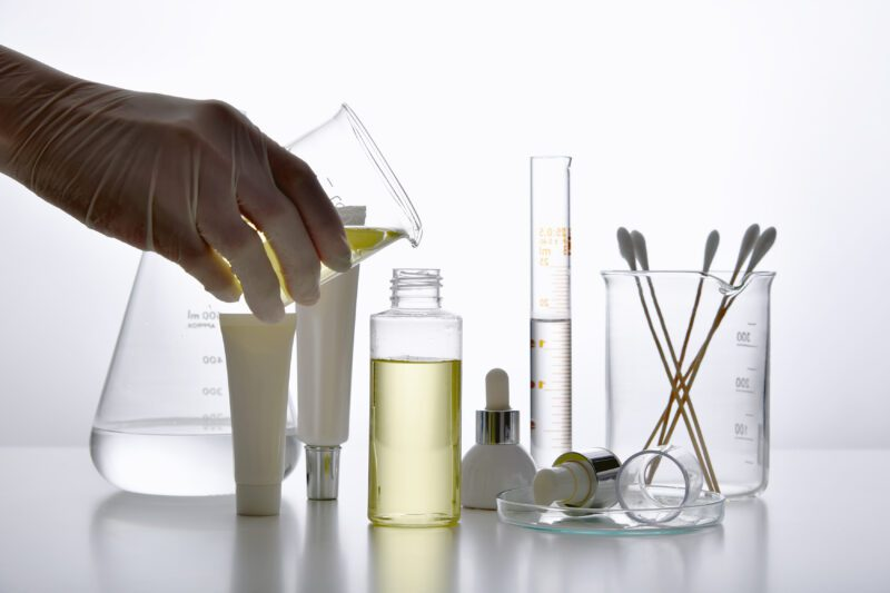 Dermatologist formulating and mixing pharmaceutical skincare, Cosmetic bottle containers and scientific glassware, Research and develop beauty product concept. - science careers