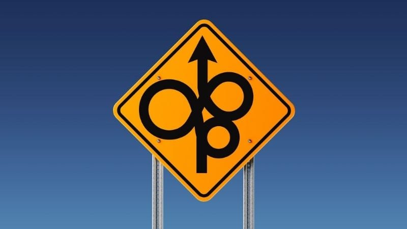 Yellow road sign showing twisted, confusing route ahead