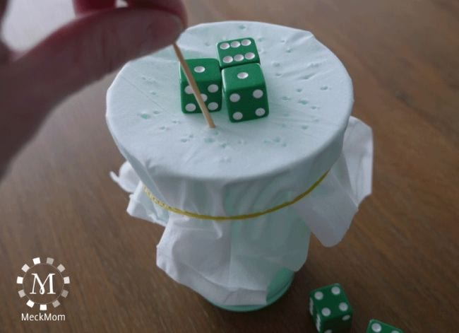 Green dice balanced on top of a cup covered with a tissue, while a student pokes holes with a toothpick (Dice Games)