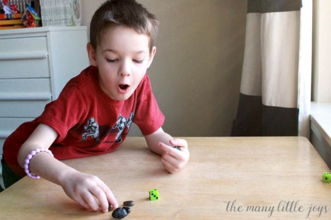 Young student rolling a dice and moving rock counters (Dice Games)