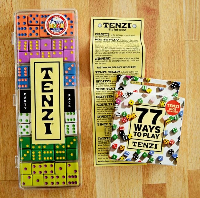 Tenzi box holding 7 colorful sets of 10 dice each, Tenzi scorecard, and deck of 77 Ways to Play Tenzi cards (Dice Games)