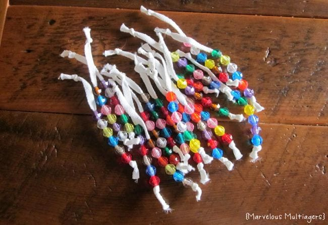 White shoelaces knotted at each end with colorful beads strung on them (DIY Fidgets)