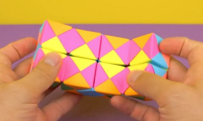 Student playing with a colorful folded paper infinity cube (DIY Fidgets)
