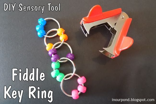 Beads strung onto keyrings attached together to make a chain, next to a staple remover; text reads Fiddle Key Ring